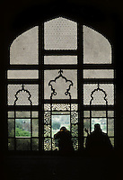 Women look out of a carved marble screen at the Lahore Fort in Lahore, Pakistan in 1996.
