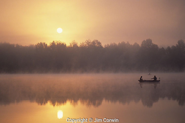 Sunrise at Lake Cassidy in fog with silhouetted fishermen in small rowboat getting ready to cast their lines, east of Marysville, Washington State USA..