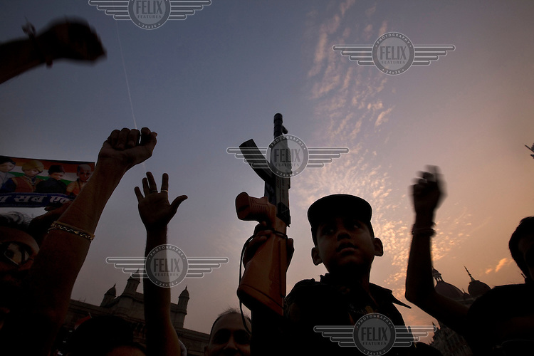 Young boy dressed as a soldier holds up his toy gun during a peace rally in front of Taj Mahal Palace Hotel after multiple terrorist attacks were launched in Mumbai on 26/11/2008..