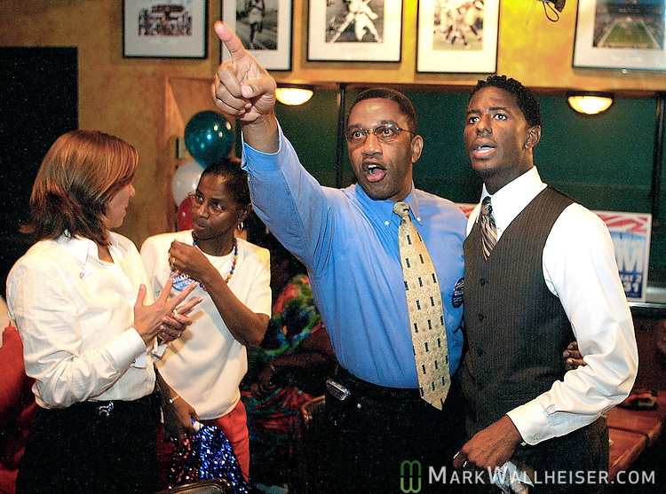 Friend and supporter Reverand Alphonso B. Whitaker (2nd from R) points out election returns to incumbent Tallahassee City Commissioner Andrew Gillum at Gillum's celebration party at Andrews on S. Adams Street.  At far left is Michelle Bono Director of Communications for the City and Gillum's assistant Angela Whitaker.