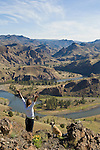 Young woman and her dog enjoy the view on a morning walk overlooking the  John Day River, Oregon.