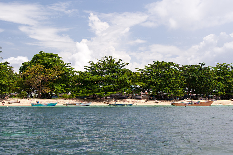 Village boats and working space nestles amongst beach-side trees on Siladen Island, in the Bunaken National Park, North Sulawesi, Indonesia.