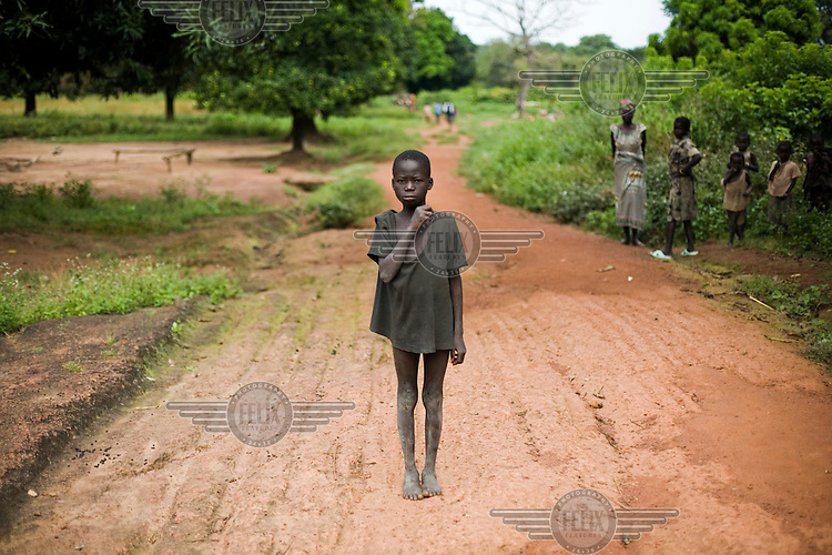 A boy stands in the road near his village while women and young children look on.