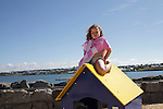 A young girl sits atop a play house at Nauthólsvík Beach in Reykjavik.