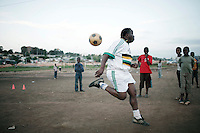 """SOWETO, SOUTH AFRICA - OCTOBER 23: Zacharia """"Computer"""" Lamula, an old football star in the local team Kaizer Chiefs teaches young boys his skills on September 15, 2007 in the Motswaledi section of Soweto, South Africa. Soccer is the most popular sport in South Africa, and a because of the upcoming World Cup 2010, the interest is increasing. For the first time the World Cup will be held on the African continent. South Africa doesn't have an organized youth soccer program and many teams and players struggle with lack of funds to buy equipment and securing money for transport to games. (Photo by Per-Anders Pettersson)....."""