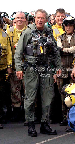 """United States President George W. Bush greets sailors on the flight deck after a successful trap aboard the USS Abraham Lincoln (CVN 72) in a S-3B Viking assigned to the Blue Wolves of Sea Control Squadron Three Five (VS-35) designated """"NAVY 1"""" on May 1, 2003. President Bush is the first sitting President to trap aboard an aircraft carrier at sea. The President is conducting a visit aboard ship to meet with the Sailors and will address the Nation as Lincoln prepares to return from a 10-month deployment to the Arabian Gulf in support of Operation Iraqi Freedom. <br /> Credit: United States Navy via CNP"""