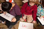 Education elementary Kindergarten students working practicing writing on dry erase boards