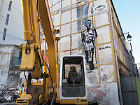 France. Department Ile-de-France. Paris. Urban development in the Belleville area (10th district). Speculation. New buildings construction. Earth-digger yellow caterpillar machine. An african warrior holding a spear in his hand has been painted on the wall. 20.05.2011 © 2011 Didier Ruef