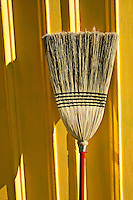 Broom against yellow wall