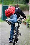 Nederland, Utrecht, 25-08-2006, Brugklasser, Brugpieper , met loodzware Eastpak rugzak , vol met zware boeken, stapt op de fiets om naar school te gaan..© foto Michael Kooren/Hollandse Hoogte..model release managed