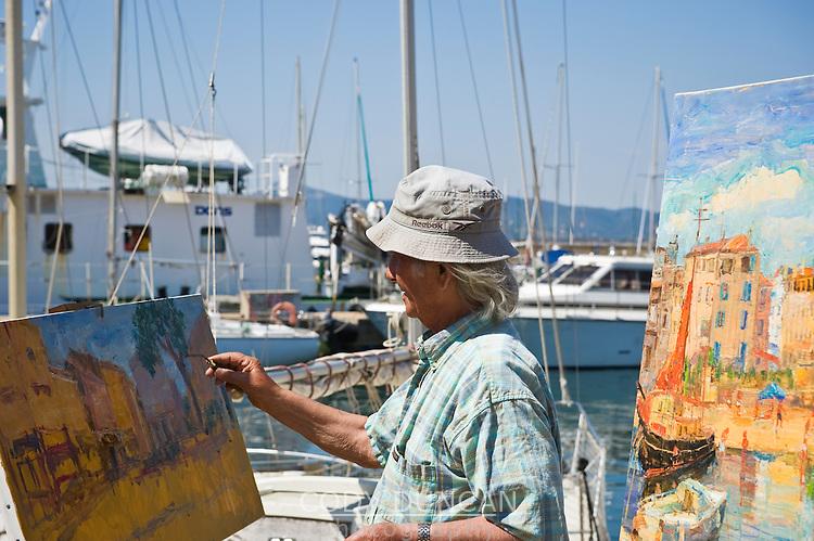 Street artist painting in harbor, Saint Tropez, France