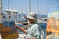 Street artist painting in harbor, Saint Tropez, France