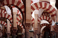Prayer Hall; Great Mosque at Córdoba; 784 - 793 AD; Córdoba, Andalusia, Spain; The twin colours, based upon the combination of brick and stone voussoirs, alternating red and white, creates an illusion of space with no defined axis, static whilst at the same time dynamic, opening in all directions at once. Only 856 of the original 1'013 columns remain, the others having been demolished during Christian reforms. Picture by Manuel Cohen