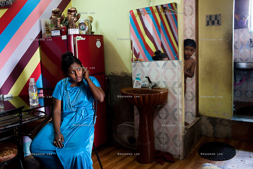 Razia Shabnam (in blue) is constantly on the phone organising the upcoming boxing competition while at home in Ekbalpore, Calcutta, West Bengal, India. Razia Shabnam, 28, was one of the first women boxers in Kolkata. She was also the first woman in her community to go to college. She is now a coach and one of only three international female boxing referees in India.  Photo by Suzanne Lee for Panos London