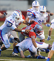 STAFF PHOTO ANDY SHUPE - Highland running back Kevin French (18) is hit by Midland Christian defensive end Reid Talley, bottom, and defensive lineman Aaron Davila (53) during the first half of play Monday, Sept. 1, 2014, at Razorback Stadium in Fayetteville.