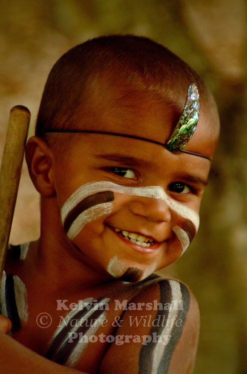 Young Aboriginal child (Tjapukai tribe) in traditional costume performing on stage.