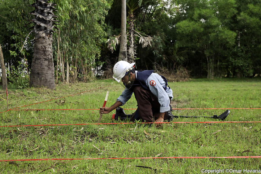 SVAY RIENG, CAMBODIA. A CMAC team member marks an UXO spot in a rural area of Svay Rieng province in Cambodia. Photography: ©Omar Havana