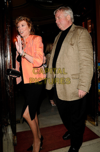 "CILLA BLACK & CHRISTOPHER BIGGINS.The ""Calendar Girls"" charity performance, Noel Coward Theatre, St. Martin's Lane, London, England, .April 20th 2009..full length orange jacket black dress brown blazer clutch bag hand waving .CAP/CAN .©Can Nguyen/Capital Pictures"