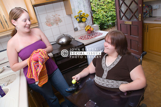 Woman with a disability chatting to non disabled friend who is drying the dishes,