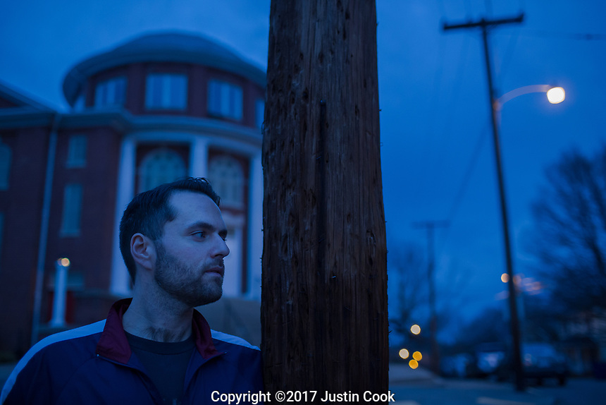 Colin Miller poses for a portrait at twilight at Green Street Church in Winston-Salem, NC. The church houses The Twin City Harm Reduction Collective, a needle exchange for addicts, which he helped found after years of struggling with addiction. (Justin Cook)