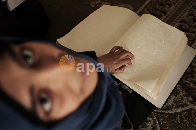A Palestinian blind girl reads and memorise the holy Quran in braille at an Islamic center in Gaza city, on January 22, 2015. Photo by Ashraf Amra