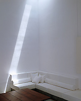 A shaft of sunlight iilluminates the stark white wall of this living space and is directed from a skylight in the ceiling