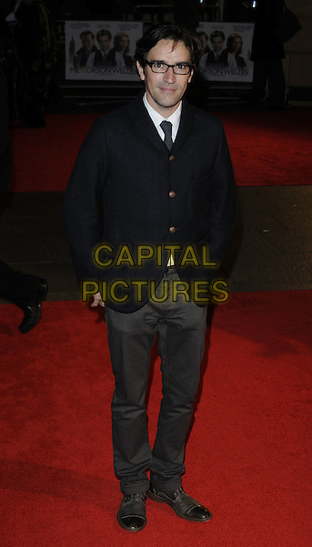 BEN CHAPLIN.'Me & Orson Welles' UK film premiere at the Vue West End, Leicester Sqaure, London, England.November 18th, 2009.full length black coat buttons tie brown hands in pockets glasses grey gray trousers .CAP/CAN.©Can Nguyen/Capital Pictures.