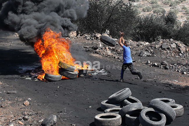 A Palestinian protester carries tires during clashes with Israeli soliders over the Jewish settlement of Qadomem at Kofr Qadom village, near West Bank city of Nablus, 19 September 2014. Palestinians are repeatedly protesting at the site against Jewish settlements in the area. Photo by Nedal Eshtayah