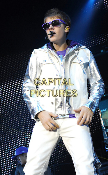 JUSTIN BIEBER.performing at the O2 Arena, North Greenwich, London, England, UK,.14th March 2011..half length white hoodie hood singing music concert on stage gig  silver microphone purple sunglasses .CAP/WIZ.© Wizard/Capital Pictures.