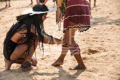 An indigenous Brazilan girl ties a beaded anklet round the leg of a fellow competitor at the International Indigenous Games, in the city of Palmas, Tocantins State, Brazil. Photo © Sue Cunningham, pictures@scphotographic.com 29th October 2015
