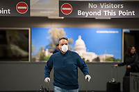 A man wears a protective mask as he and other passengers arrive from Dubai after a 14-hour flight on Emirates flight 231, at the international terminal at Dulles International Airport in Dulles, Va., Monday, March16, 2020. Some people are taking the precaution of wearing face masks as they arrive to be greeted by family and or friends. Credit: Rod Lamkey / CNP/AdMedia