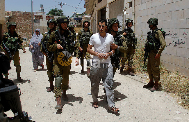 Israeli troops detain a Palestinian man, who the Israeli military said he was throw a molotov cocktail towards Israeli troops, in the West Bank city of Hebron 01 June 2016. Photo by Wisam Hashlamoun
