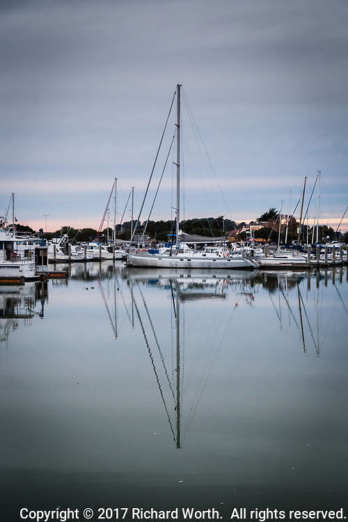 Overcast skies hover over  sailboats and their reflections in the equally gray waters of the San Leandro Marina while a faint hint of sunset's glow warms the horizon, along San Francisco Bay, Christmas evening, 2017.