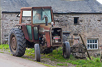 Old Massey Ferguson tractor outside a stone barn, Cumbria.