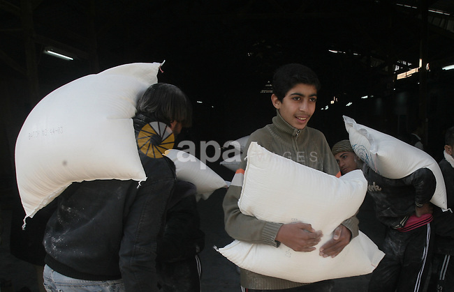 A Palestinian man holds a sack of flour at monthly food aid at a UN distribution center in Rafah southern Gaza city, on Jan. 11, 2014. The UN Relief and Works Agency (UNRWA) will reduce some of its services for Palestinian refugees due to budget deficit and shortage of donor funds. Photo by Eyad Al Baba