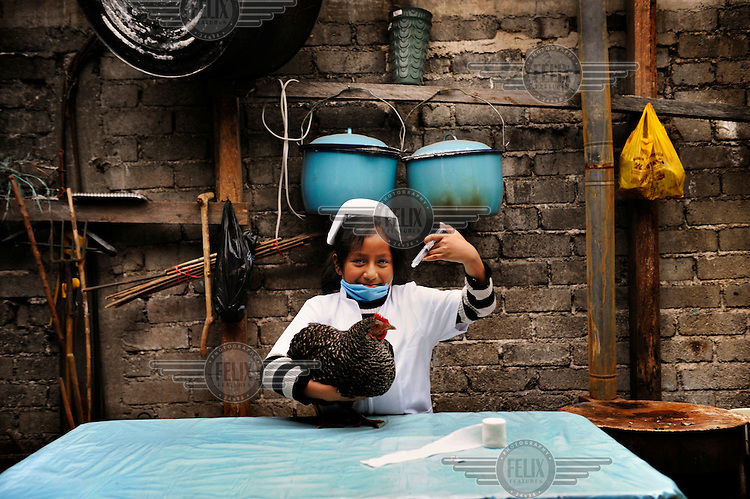 """Djarida, dressed up as a veterinarian, holds a chicken and pretends to inject it with a syringe..Djarida is 8 years old and lives in San Cristobal de las Casas in Chiapas, Mexico. She is from a Mayan family background. Mayans are one of the indigenous peoples of Mexico, many of whom today are poor and disadvantaged. Djarida's father left the family home and her mother works as a housekeeper in the city. Djarida loves all animals, especially dogs. """"Many girls are not allowed to go to school or only for a short time. Then they are required to help at home, to get married or to work. I'm happy going to school every day. When I grow up I want to be a veterinarian. I have to study hard but I'm sure I will succeed."""" .."""