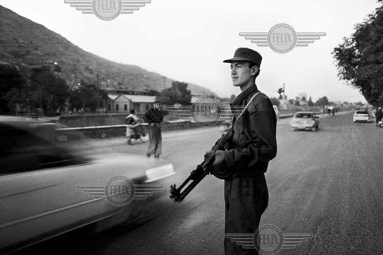 An Afghan policeman armed with a light machine gun directs traffic in war-torn Kabul onTuesday,  July 2, 2002.
