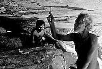 A TRIBAL ELDER RETAOUCHING ANCIENT ABORIGINAL ROCKART DEEP INSIDE ARNHEM LAND,IN THE NORTHERN TERRITORY,AUSTRALIA