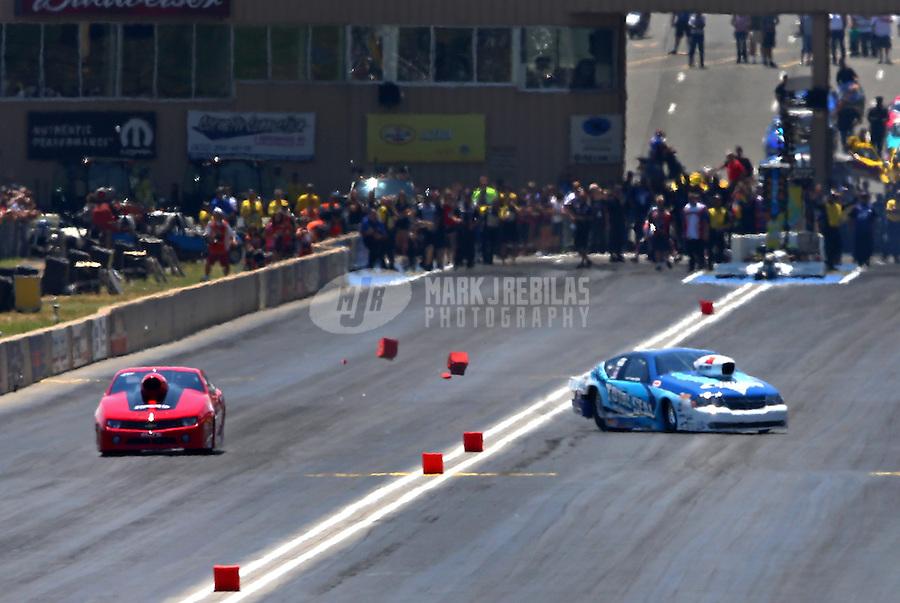 Jul. 21, 2013; Morrison, CO, USA: NHRA pro stock driver Matt Hartford (right) crashes alongside Rickie Jones during the Mile High Nationals at Bandimere Speedway. Hartford was uninjured. Mandatory Credit: Mark J. Rebilas-
