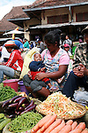 A mother and her baby selling aubergine, carrots and green beans at the Analakely market in Antananarivo in Madagascar