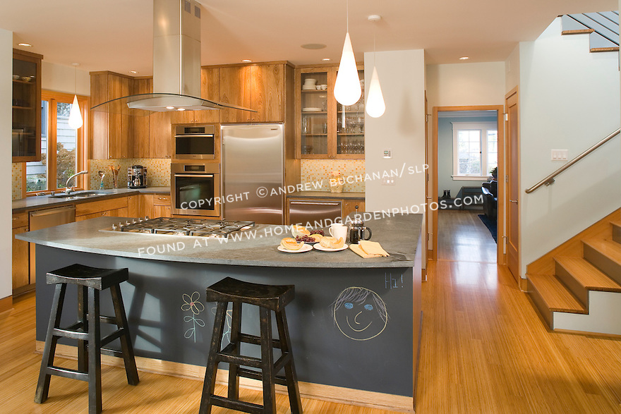Hickory cabinets and bamboo floors add to the unusual wood grains in this Seattle residential kitchen remodel, while a slate chalkboard mounted on the kitchen island provides fun, creative space for the family's toddler.  Stairs to the right lead to the second story addition, while the living room at the front retains many of its original period details.