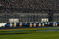 The field races on the back straight led by Kasey Kahne (#9).