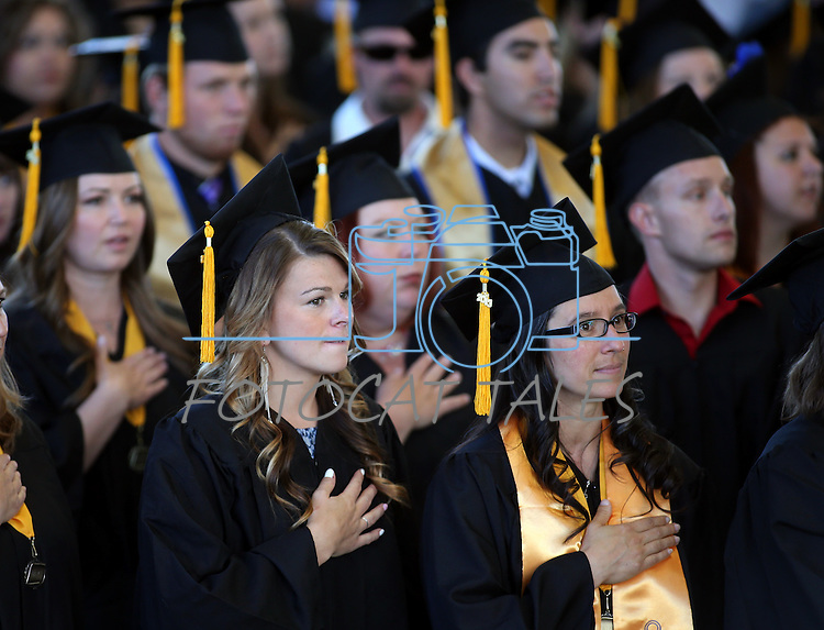 Emily Nagel and Jessica Leman listen to the National Anthem during the 2013 Western Nevada College Commencement at the Pony Express Pavilion, in Carson City, Nev., on Monday, May 20, 2013. .Photo by Cathleen Allison
