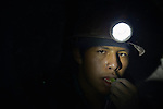 A miner inside a mine in Potosi, Bolivia, chewing coca leaves. The mine produces silver and other metals.