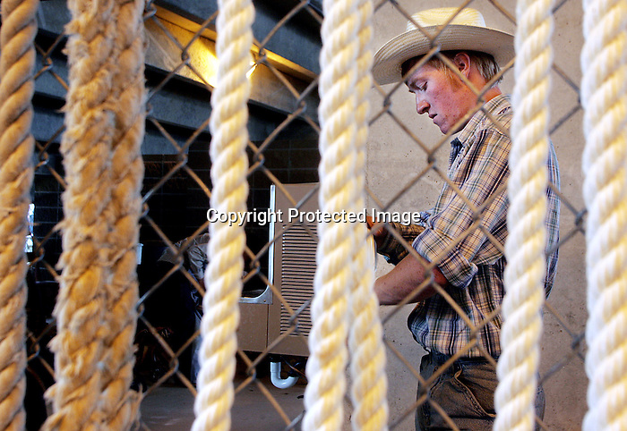 MICHAEL SMITH/WTE..Ropes frame Saddle bronc rider Josh Koshell as he prepares for his ride in the comboy ready area Saturday.