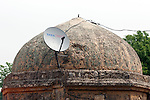 Satellite television dishes and electricity lines sit on the onion shaped domes of unnamed Lodhi period tombs that are now homes which are built into part of an ancient tomb complex at Nizamuddin in Delhi, India. The Archaeological Survey of India has been on a campaign to evict people who have illegally made the tombs their homes throughout the city in recent times but is facing stiff opposition from the residents.
