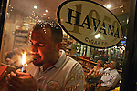 9/23/06 Al Diaz / Miami Herald Staff--Mike Olivares lights up a cigar at his shop Habana Cuba Cigar Company in Miami Lakes. Mike was reared in Miami Lakes by his Cuban parents Luis and Marissa Olivares, at right. His parents still live in Miami Lakes.