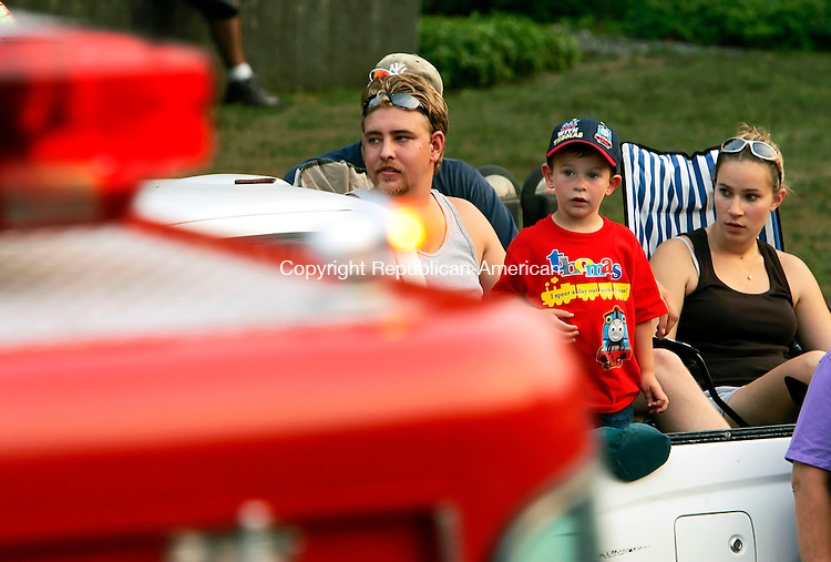 THOMASTON, CT - 13 AUGUST 2005 -081305JS03-- Jacob Sharr, 3, center of Terryville watches fire trucks drive by as he sits in the back of a truck with Mike Grady and Colleen Weeks of Thomaston during the annual Thomaston Volunteer Fire Department's parade Saturday in downtown Thomaston. The parade was held on the final night of the annual carnival which is one of the biggest fund raisers for the department.  --Jim Shannon Photo--Jacob Sharr; Colleen Weeks, Mike Grady, Thomaston are CQ
