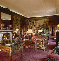 The luxurious panelled drawing room is hung with tapestries