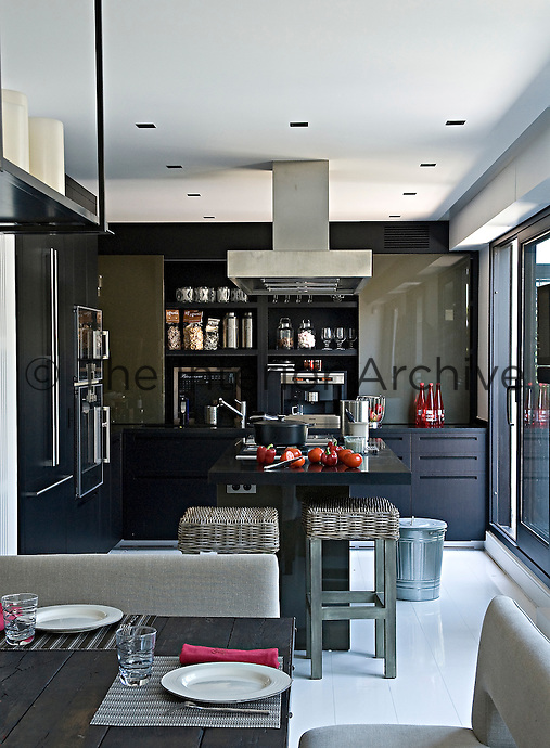 In this elegant kitchen the cupboards are constructed from blackened oak with sliding doors made with a constrasting lacquered finish